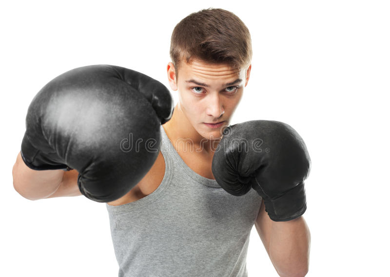 Boxer throwing a punch. Portrait of young boxer throwing a punch at the camera isolated on white background royalty free stock photography