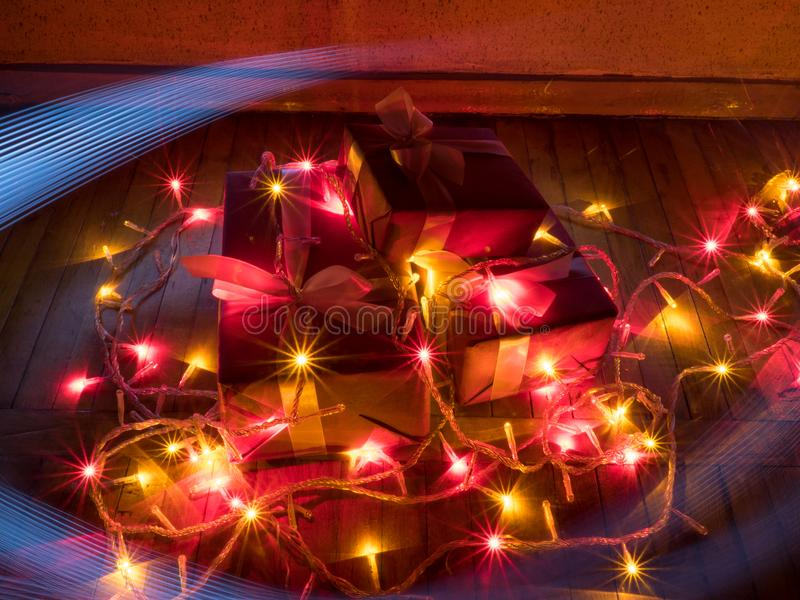 Boxes with Christmas gifts with garlands with christmas lights and traces from drawing by light stock images