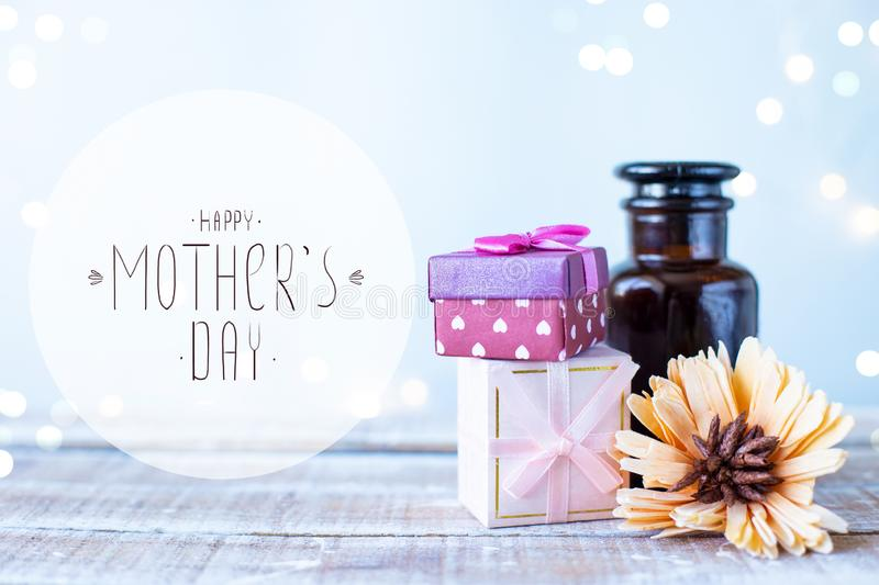 Boxes with gifts, a bouquet of flowers, cosmetic oil on a light blue background with the inscription Happy Mothers Day stock images