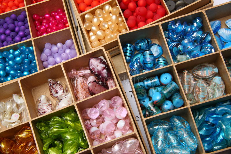 Boxes of jewellery beads. Closeup of colorful jewellery beads in square boxes royalty free stock photography