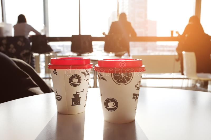 2 boxes of paper disposable cups with red led on the table in the cafe. Morning. Coffee for Breakfast. Coffee to go. The shadows royalty free stock photos