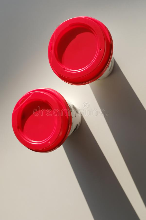 2 boxes of paper disposable cups with a red lid on the table in the cafe. Coffee to go. Morning. Coffee for Breakfast. 2 cups of stock images
