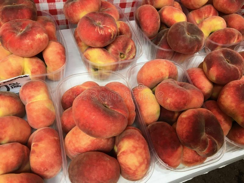 Boxes of saturn peaches sold at a market in Croatia.  The flat peach Prunus persica var. platycarpa royalty free stock photos