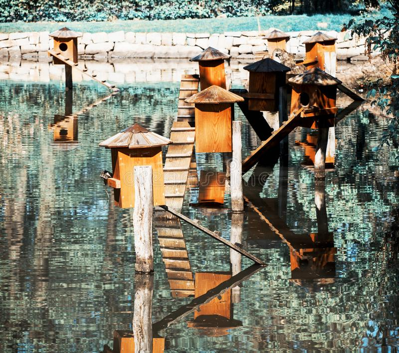 Boxes for waterfowl nesting on water. Boxes for waterfowl nesting on the water. Natural theme. Teal and orange photo filter stock photography