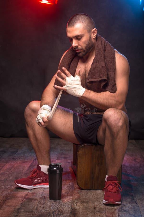 Boxeur d'homme attachant du ruban adhésif vers le haut de ses mains Athlète se préparant au combat photo stock