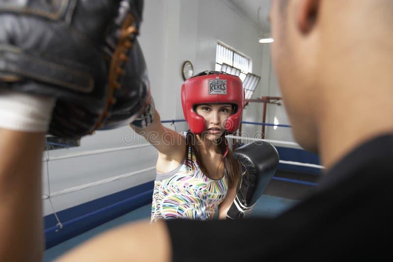 Boxeur féminin frappant sa cible en anneau photos stock