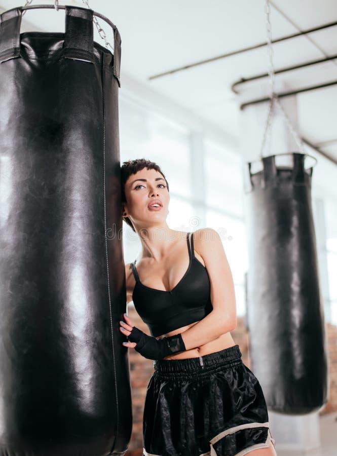 Boxeur féminin magnifique dans des clothers de gymnase à côté de grand sac de sable noir photographie stock