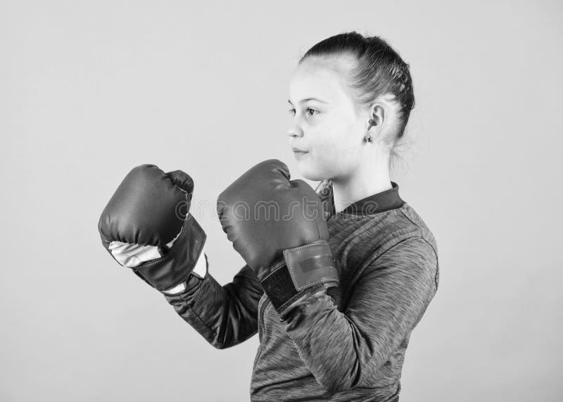 Boxeur mignon sur fond bleu Contrairement au stéréotype Enfant de boxe dans des gants de boxe Confiance Jouir de image stock
