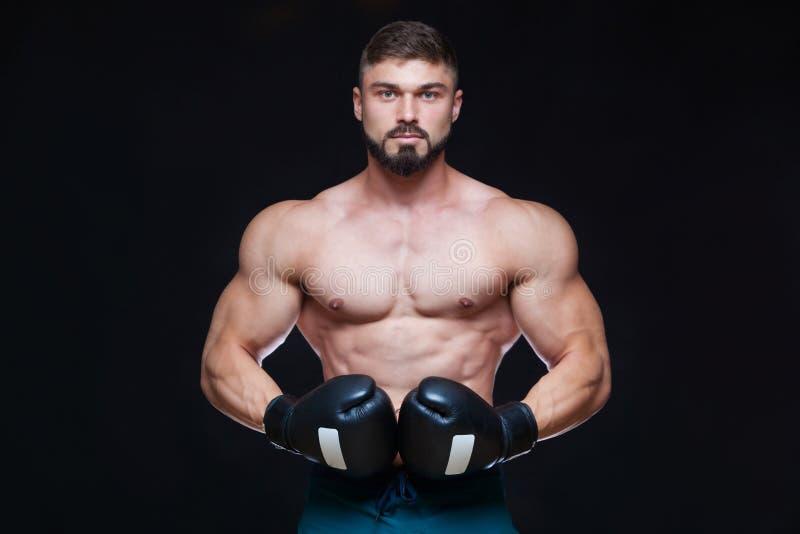 Boxeur musculaire fort dans les gants de boxe noirs D'isolement sur le fond noir images stock