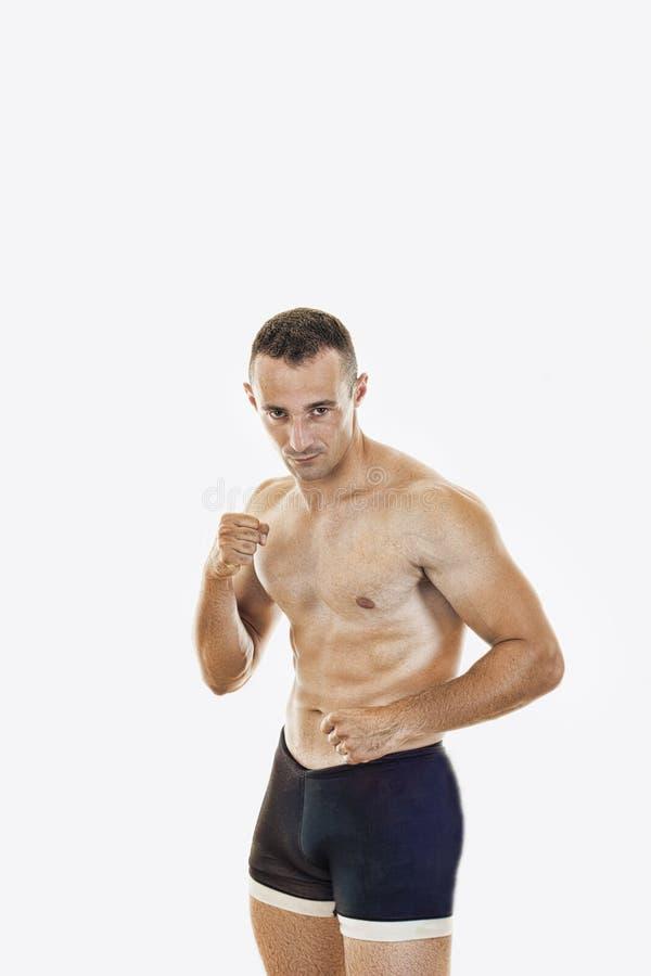 Boxeur musculaire professionnel se tenant dans la pose de combat dans les massifs de roche nus image stock