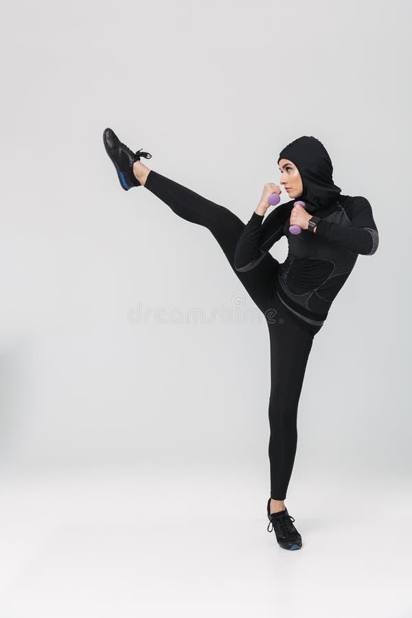 Boxeur musulman de combattant posant au-dessus du fond blanc de mur pour faire des exercices avec des haltères photos stock