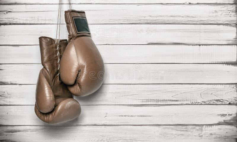 Boxhandschuhe, die an der hölzernen Wand hängen