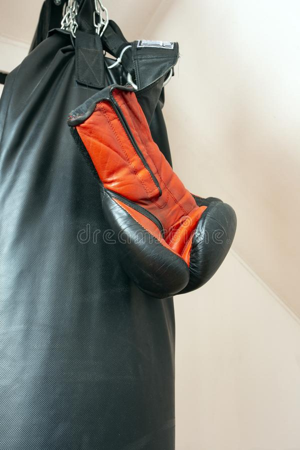 Boxhandschuhe und Sandsacknahaufnahmesportkonzept lizenzfreie stockfotos
