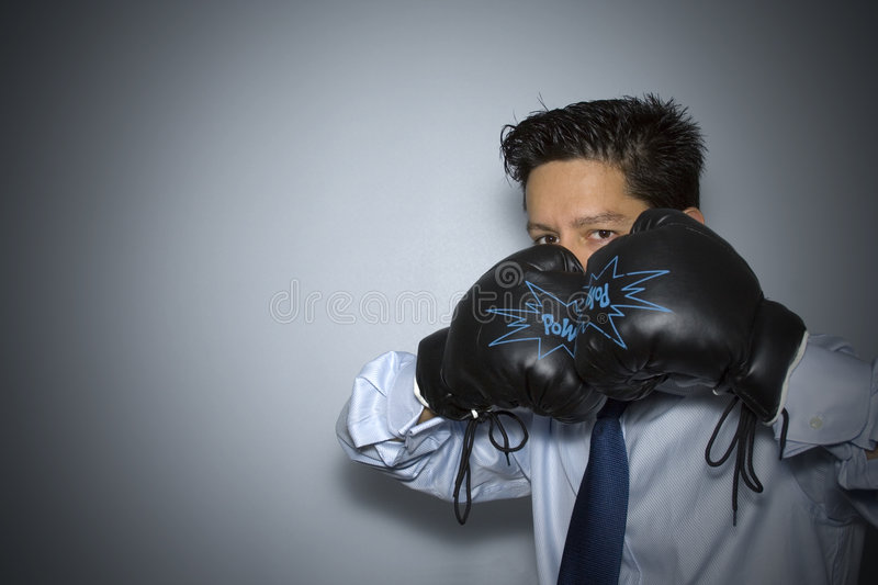 Boxing in business. Aggressive businessman ready to punch everyone stock images