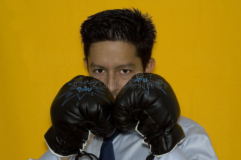 Boxing in business. Aggressive businessman ready to punch everyone stock image