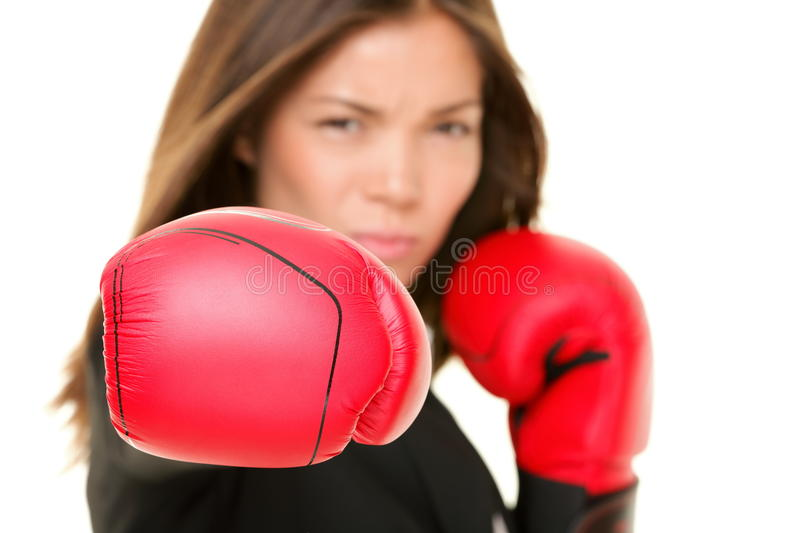 Boxing business woman. Punching towards camera wearing boxing gloves. Focus on boxing glove. Businesswoman isolated on white background stock photography