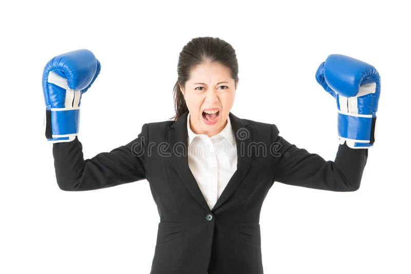 Boxing business woman showing aggressive. Boxing gloves business woman angry showing aggressive female businessperson flexing muscles wearing boxing gloves stock photography