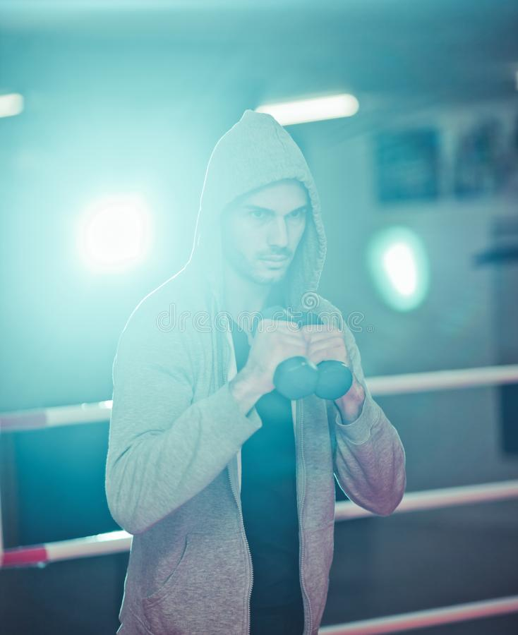 Boxing concept. Boxer man during boxing exercise. With dumbbells in boxing ring royalty free stock images