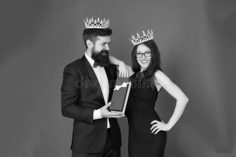 Boxing day. Bearded man and happy woman in crown. couple in love. date. business look. anniversary party gift box royalty free stock photos