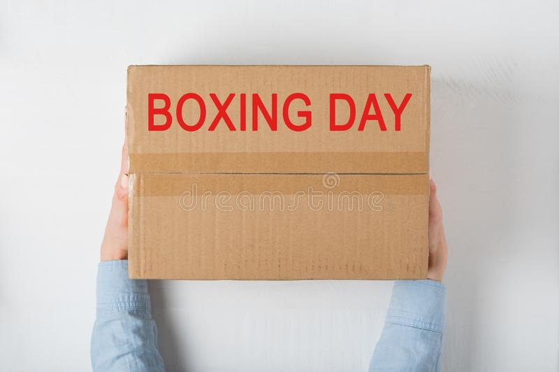 Boxing day. Large cardboard in female hands. White background stock images