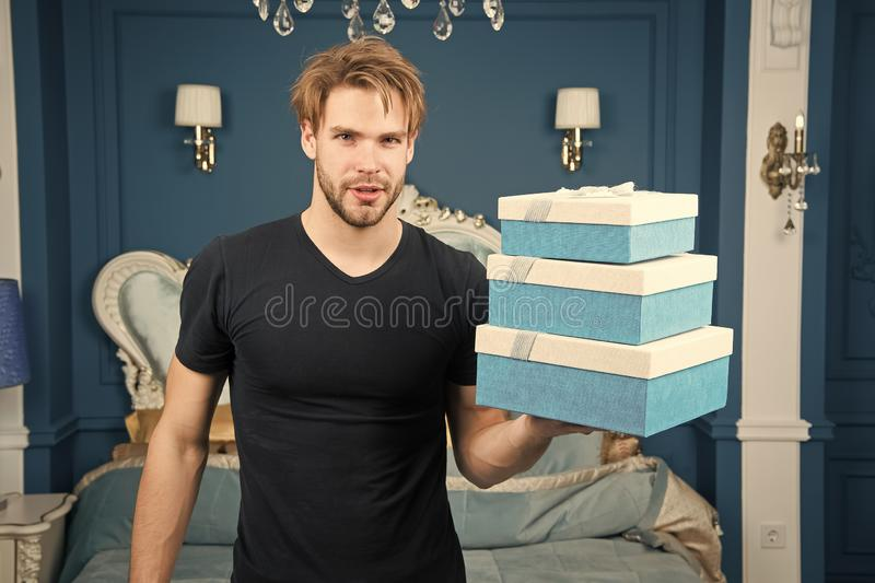 Boxing day. Man hold present boxes in luxury interior. Handsome man offer luxury goods. The spirit of luxury lifestyle. Happy boxing day stock photo