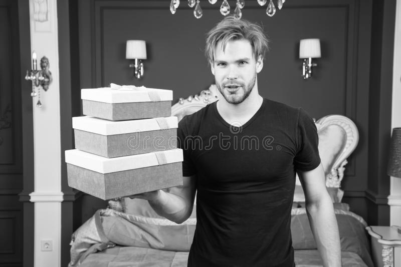 Boxing day. Man hold present boxes in luxury interior. Handsome man offer luxury goods. The spirit of luxury lifestyle. Happy boxing day royalty free stock photos