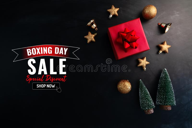Boxing day sale with Christmas present and xmas decoration on black background royalty free stock photos