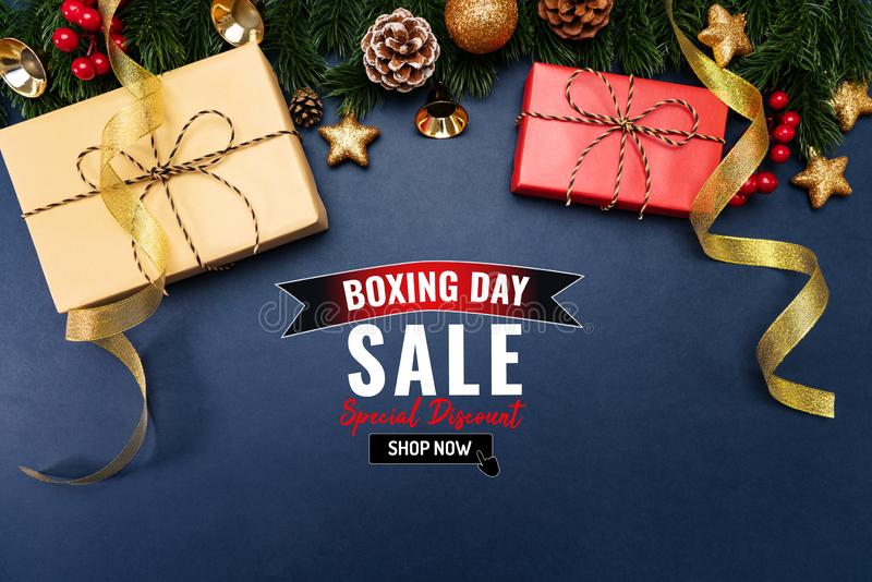 Boxing day sale with Christmas present and xmas decoration on blue background royalty free stock photography
