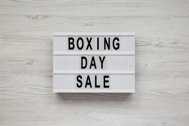 `Boxing day sale` words on a modern board on a white wooden background, top view. Overhead, from above, flat lay.  royalty free stock photography