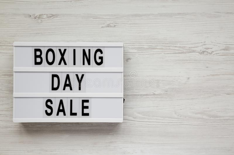 `Boxing day sale` words on a modern board on a white wooden background, top view. Overhead, from above, flat lay. Copy space.  stock photo