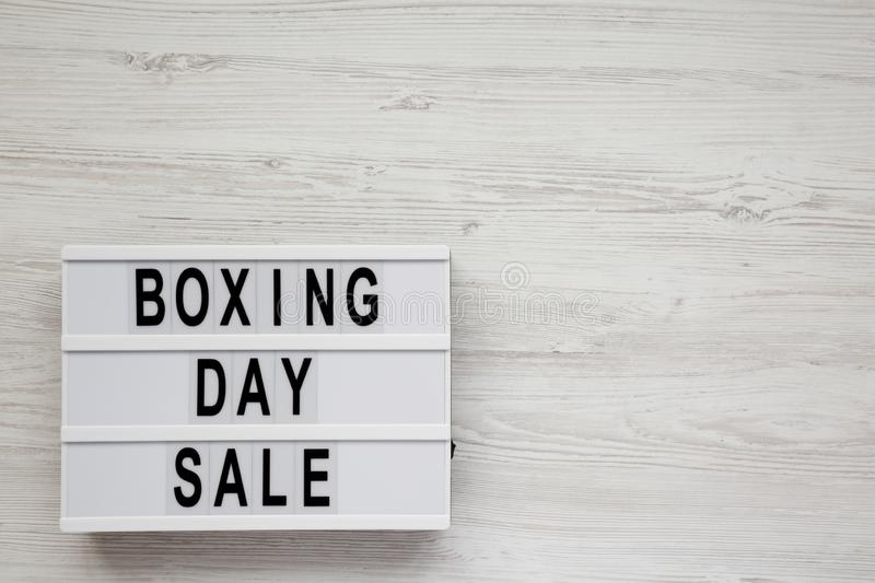 `Boxing day sale` words on a modern board on a white wooden surface, top view. Overhead, from above, flat lay. Space for text.  royalty free stock photos