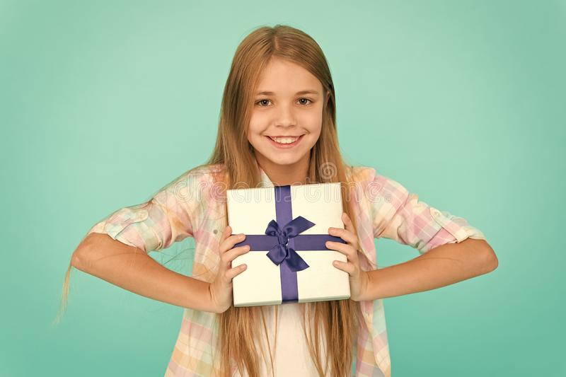 On boxing day. Small girl after shopping for gift. Little shopaholic with present wrapped in box. Small child holding. Gift box tied with ribbon bow. Cute royalty free stock photo