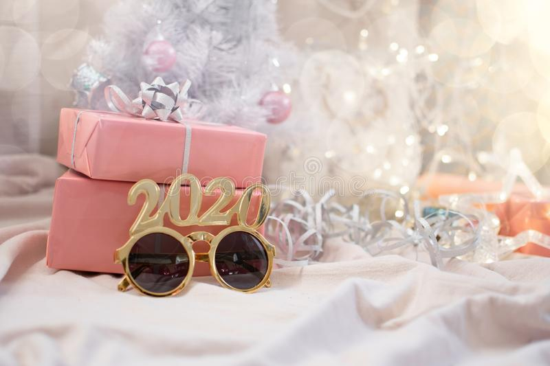 Boxing day 2020. Trendy holiday background with pink rose gold gift boxes, carnival  glasses 2020 and white Christmas tree stock photo