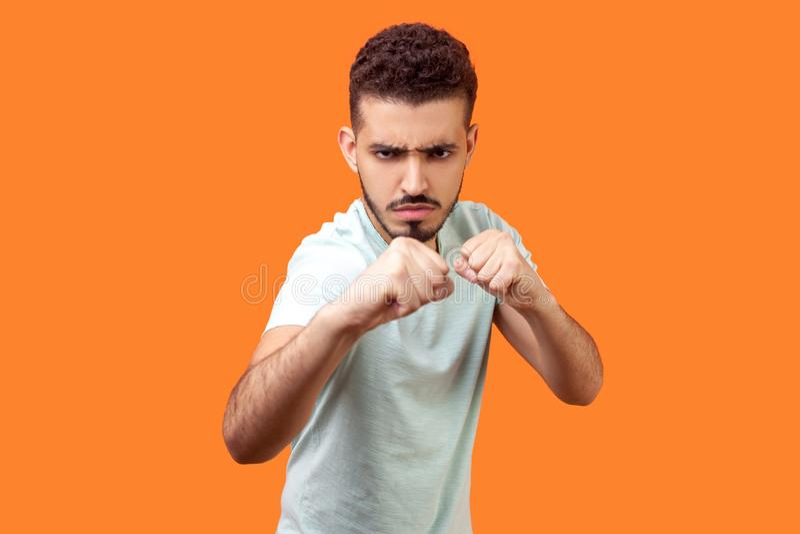 Boxing e autodefesa Retrato do fraco mordomo furioso mantendo os punhos cercados, prontos para se defender na luta isolado em lar imagens de stock