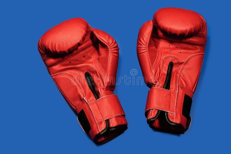 Boxing gloves. Red boxing gloves on a blue background stock images