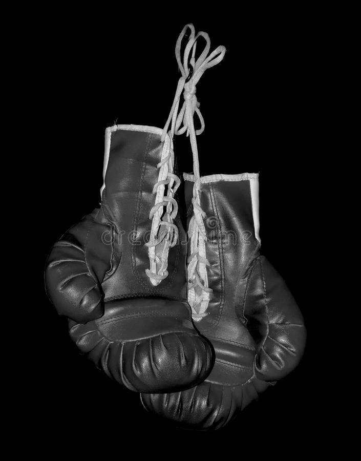 Boxing gloves. Greyscale image of hanging boxing gloves on black background stock photography