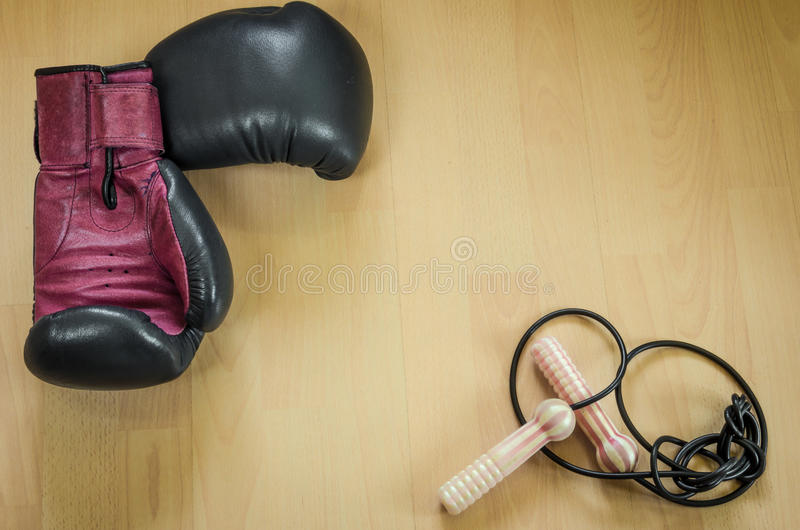 Boxing gloves and skipping rope. On a wooden background royalty free stock photo