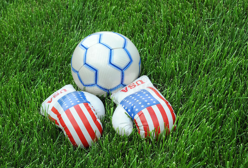 Boxing Gloves and Soccer Ball on Green Lawn stock photo