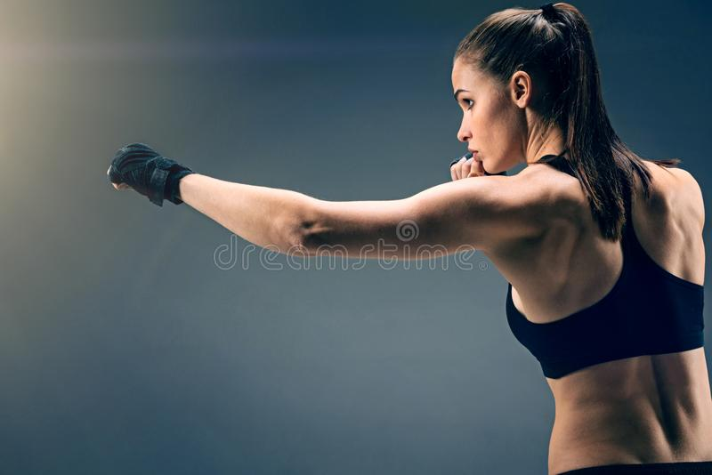 Side view of young sportswoman punching over background stock photography
