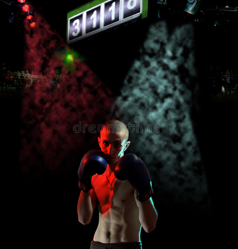 Boxing man and audience. Boxing man in a colour fog before the audience royalty free stock photography