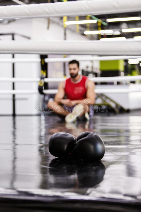 The Boxing Man. Defocused boxing man sitting in the ring, black pair of gloves royalty free stock photography