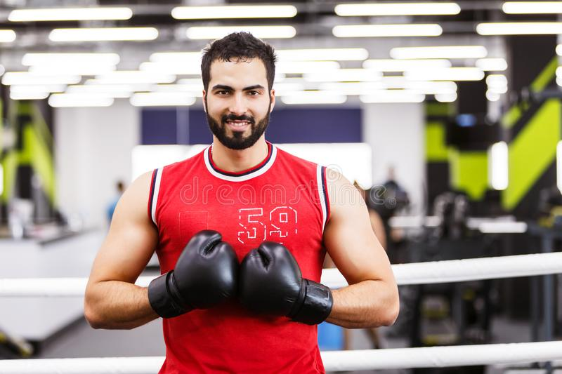The Boxing Man. Portrait of handsome boxing man wears black gloves in the ring royalty free stock image