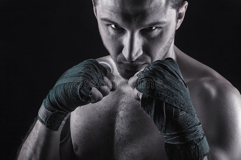 Boxing man. Ready to fight. Boxer with strong hands and clenched fists on a black background stock photography