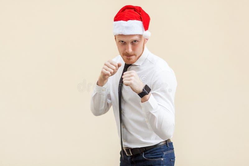 boxing O homem de negócios adulto novo do gengibre no chapéu vermelho de Santa, apronta-se para a luta na luz - fundo alaranjado fotos de stock