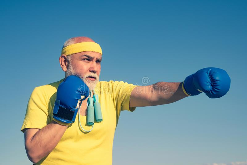 Boxing. Portrait of a determined senior boxer over blue sky background. Senior man wearing boxing gloves. Boxer with. Boxing glove royalty free stock image