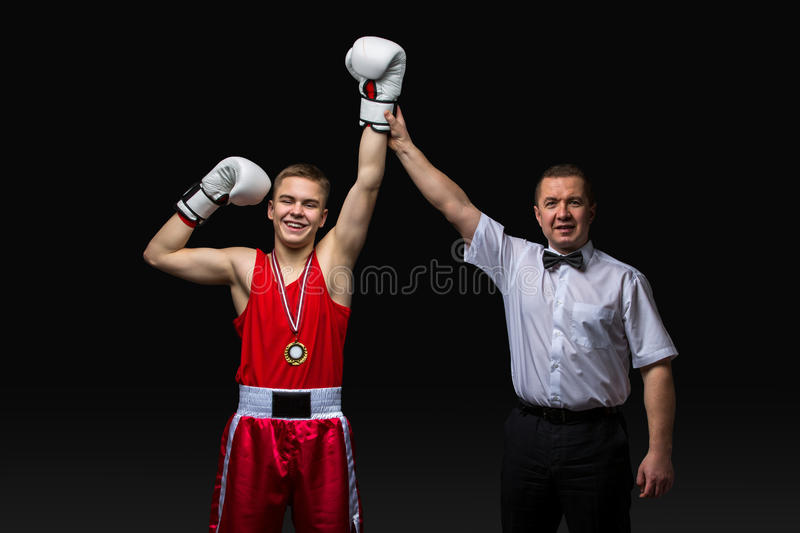 Boxing referee gives medal to young boxer. Boxing referee gives medal to young teen boxer in red form and white gloves. Winner. Studio shot on black background royalty free stock images