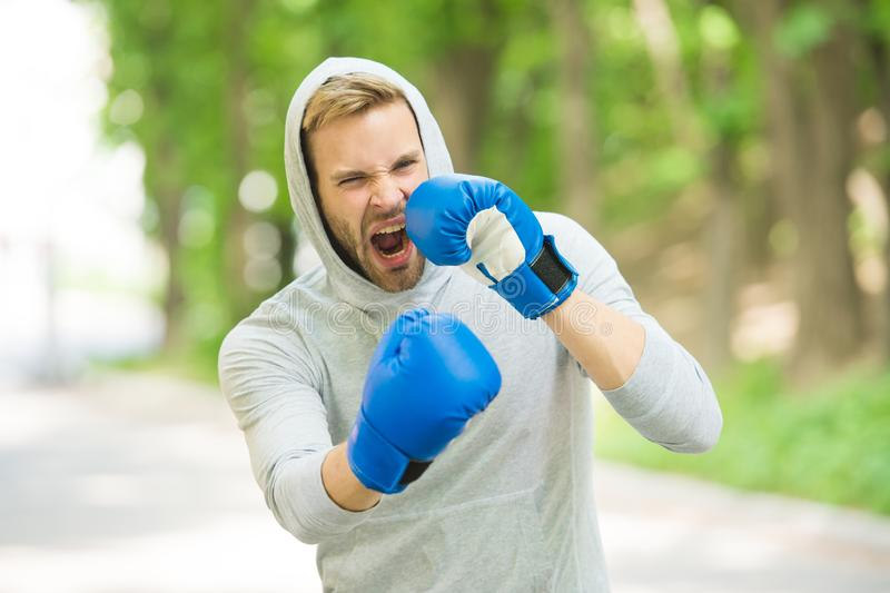 Boxing training endurance. Man athlete concentrated face with sport gloves practicing boxing nature background. Boxer. Ready to fight. Sportsman boxer training royalty free stock photos