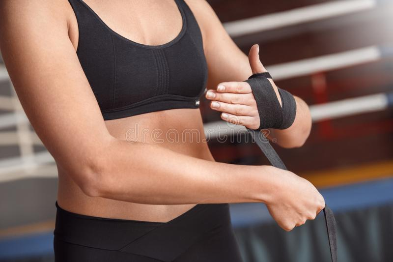 Boxing. Woman boxer putting bandage around wrist near ring close-up royalty free stock photography