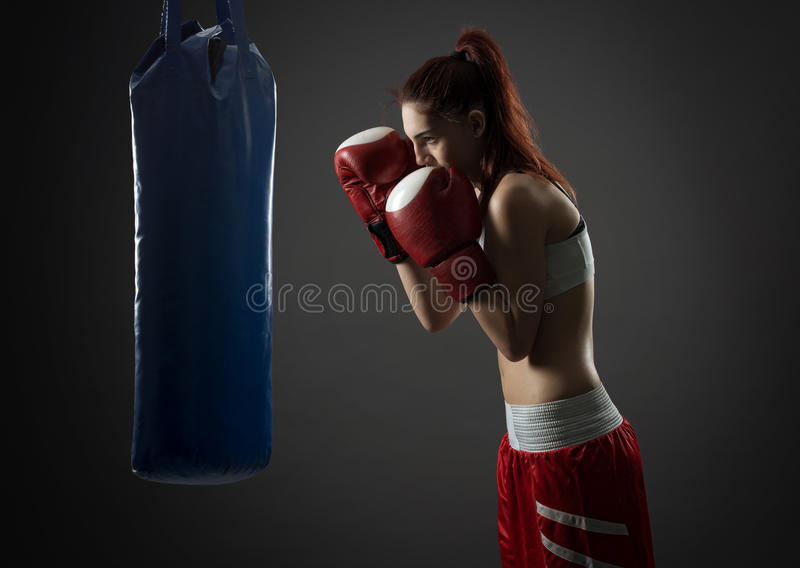 Boxing woman exercises with punching bag stock image
