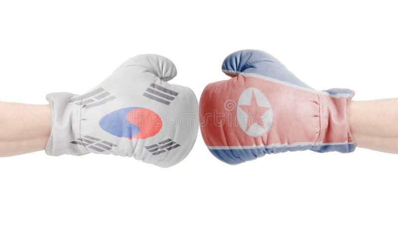 Boxninghandskar med den Sydkorea och Nordkorea flaggan Sydkorean vs det Nordkorea begreppet royaltyfria bilder